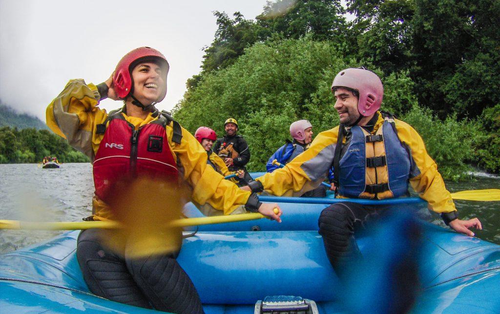 casal sorrindo no bote de rafting no rio trancura em Pucón, Chile