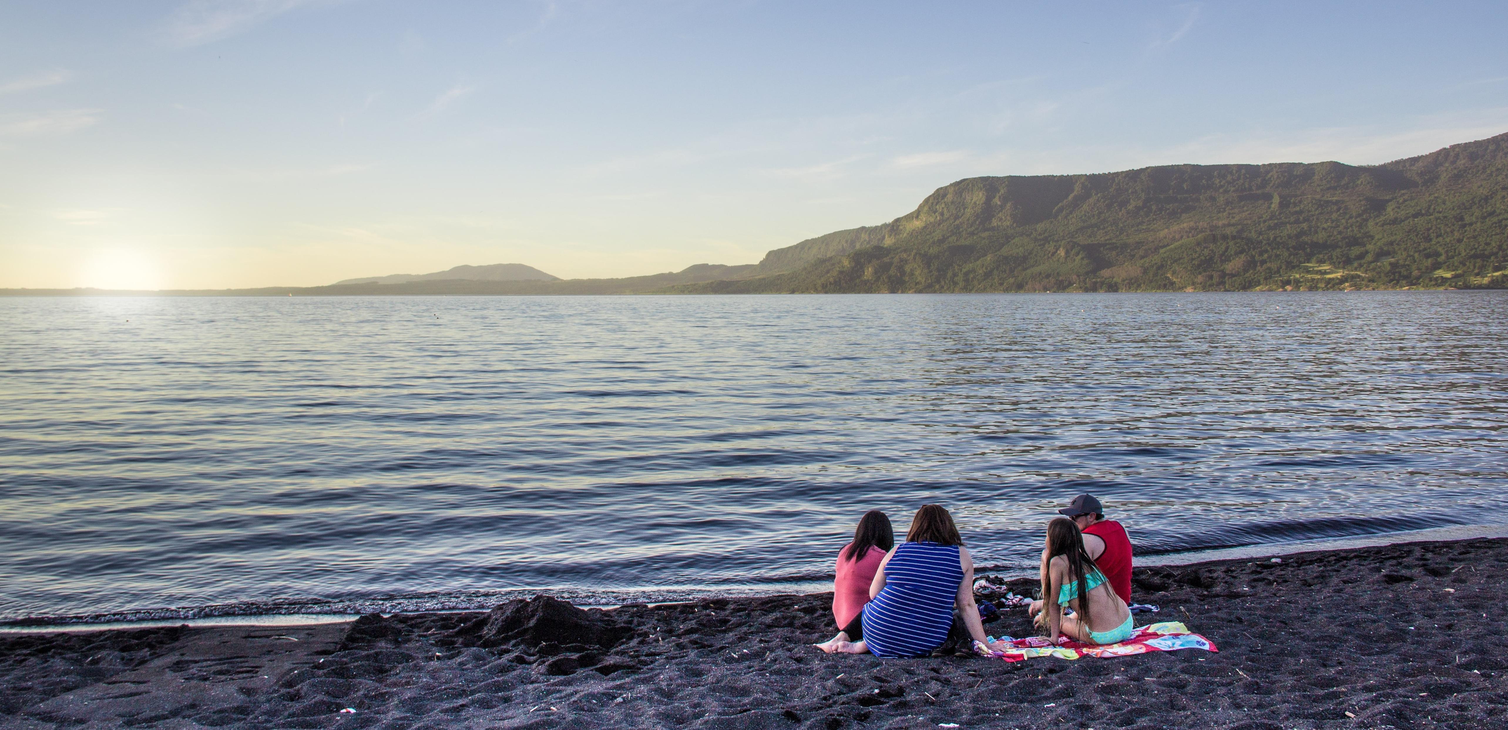 familia vendo o por do sol na beira do lago villarica, em Pucón, Chile