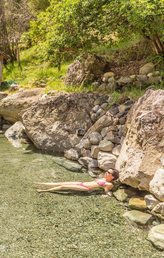 Mulher na piscina de com bordas de pedra e árvores ao fundo. Los Pozones, perto de Pucón