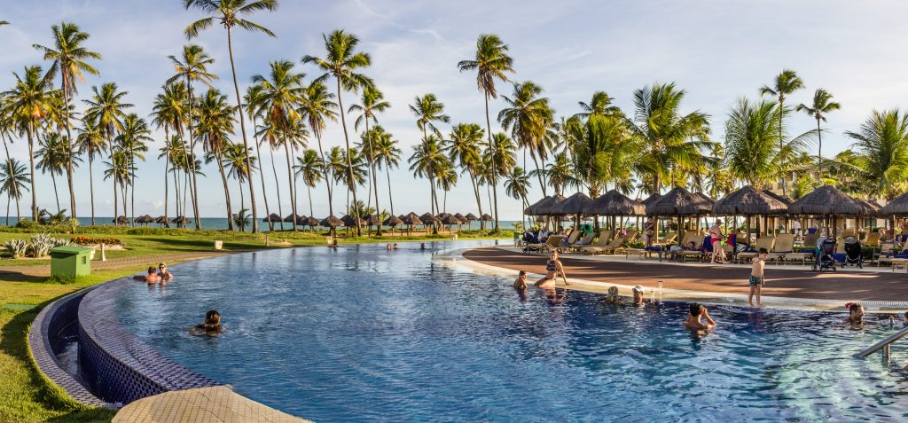 piscina com coqueiros ao fundo no iberostar praia do forte