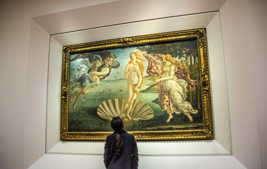 Menina de costas olhando o quadro Nascimento de Vênus, de Botticelli. Vale a pena comprar o Firenze card.
