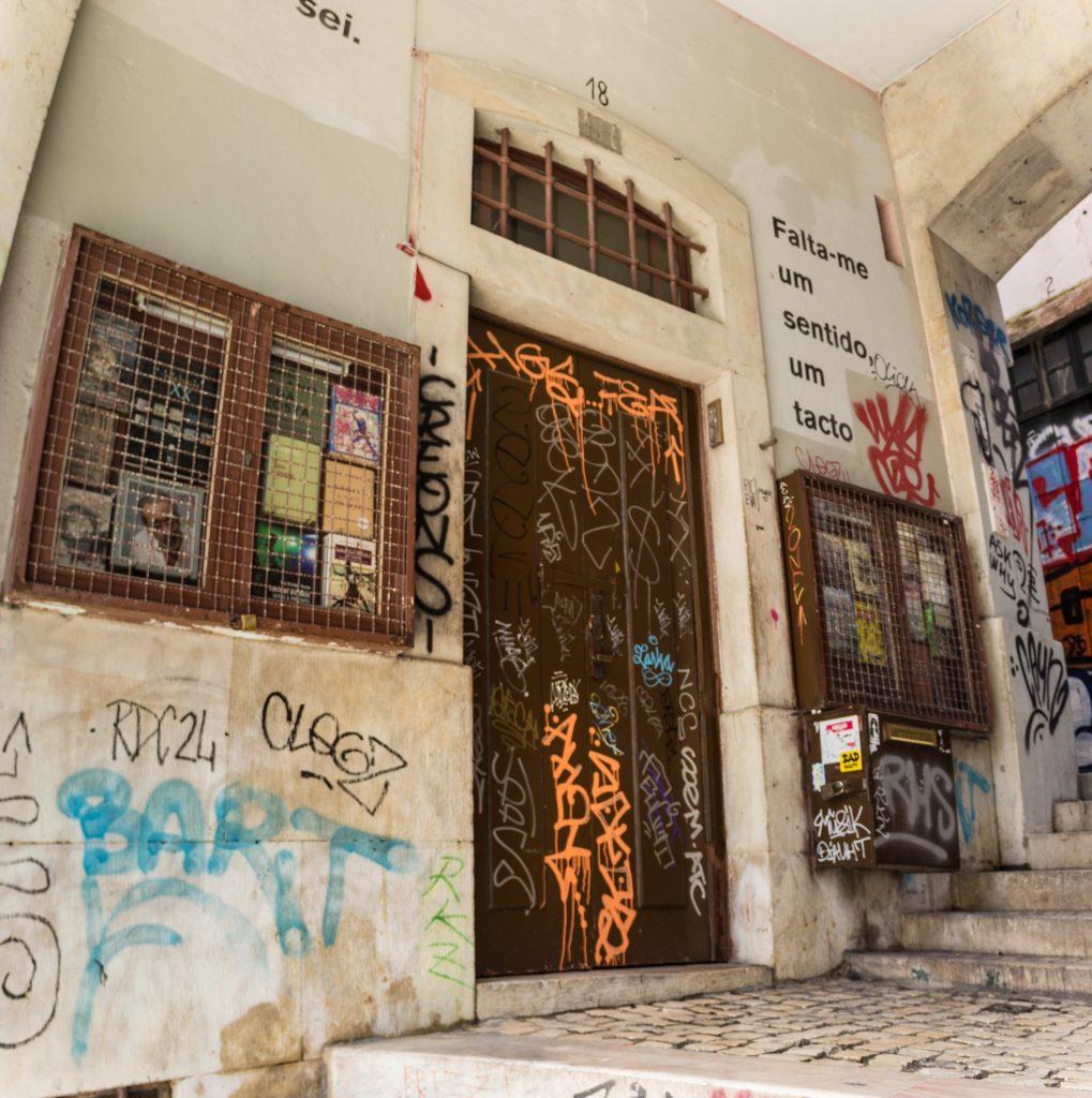 Fachada de loja em Lisboa com a porta fechada e paredes pichadas