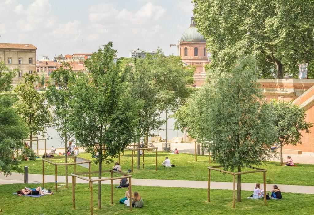 pessoas sentadas na grama entre as árvores - slow travel