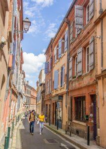 Casal caminhando em uma rua estreita do centro histórico de Toulouse - slow travel