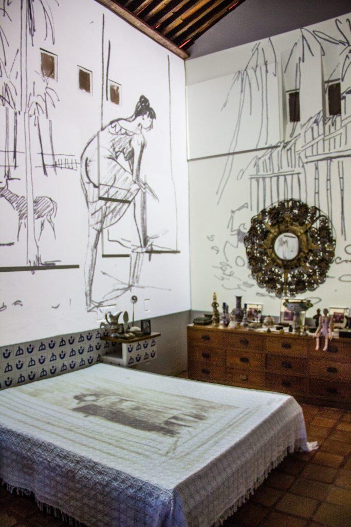 quarto com cama de casal e cômoda, com imagens projetadas nas paredes na casa do rio vermelho