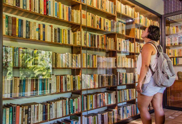 mulher de costas olhando uma estante de livros na casa do rio vermelho