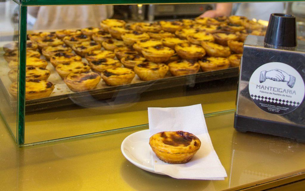 vitrine de vidro com pastéis de nata e um pastel de nata em prato no balcão - restaurante barato em Lisboa