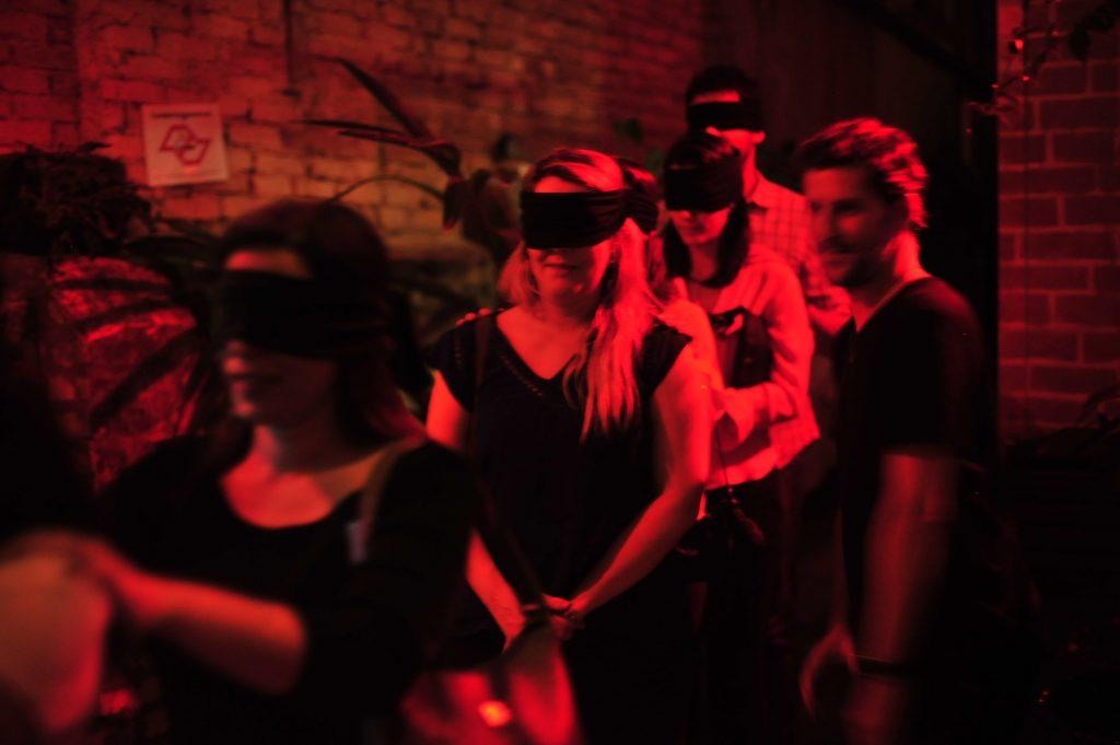fila de pessoas de olhos vendados no jantar no escuro
