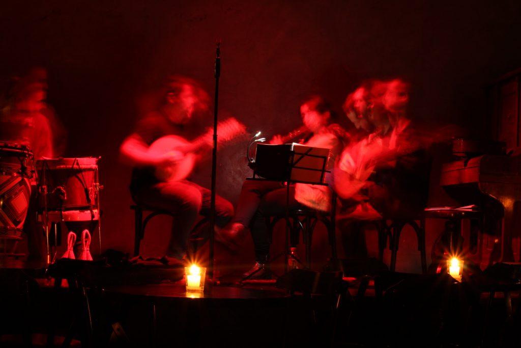 quatro musicos tocando violao, flauta e tambor no jantar no escuro