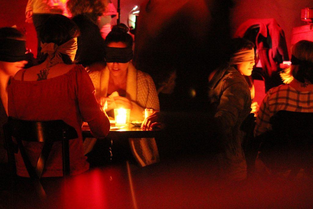 pessoas sentadas a mesa e vendadas no jantar no escuro