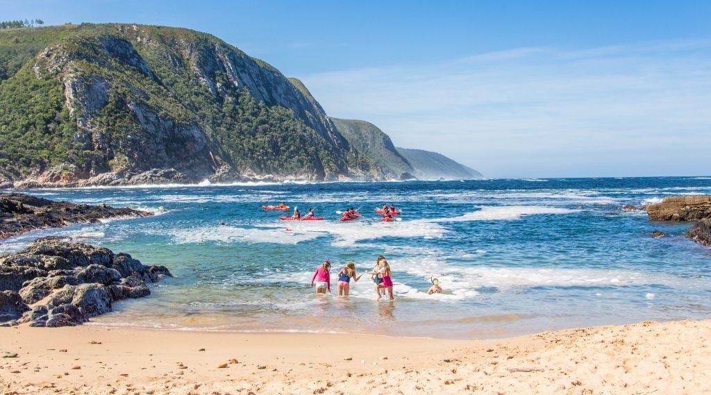 Criancas brincando no mar e kayaks, montanhas ao fundo