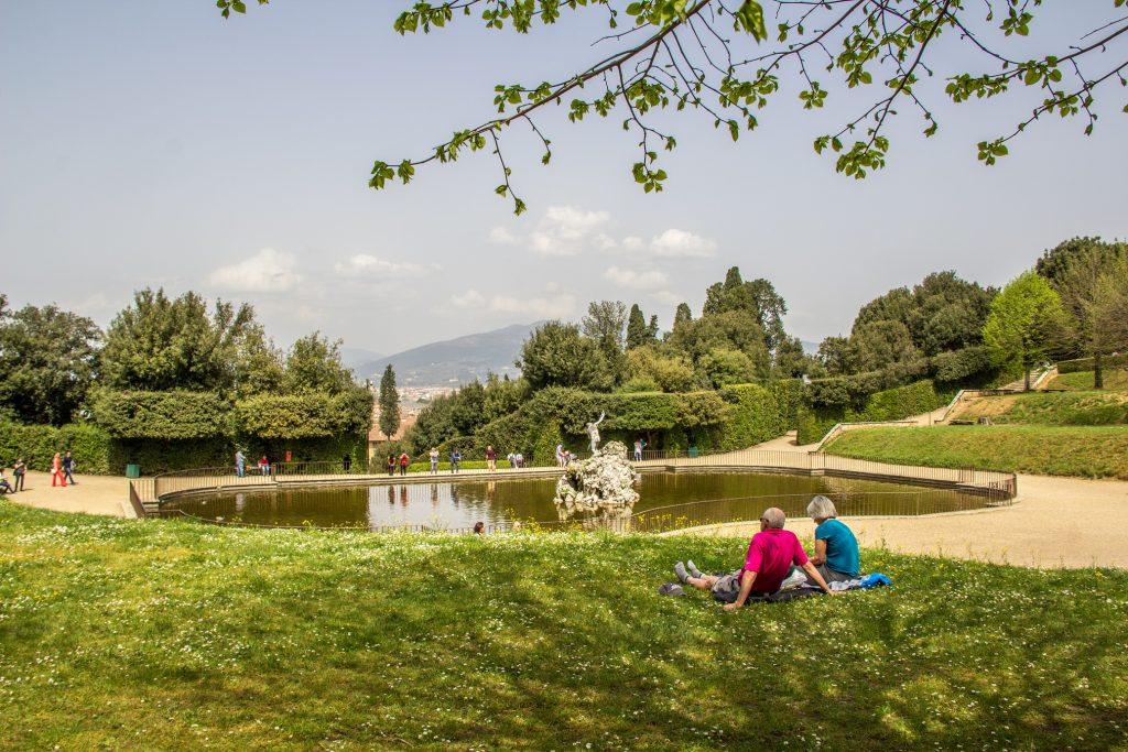 Casal sentado diante de uma fonte nos Jardins de Boboli com o Palazzo Pitti ao fundo - roteiro de 3 dias por Florença