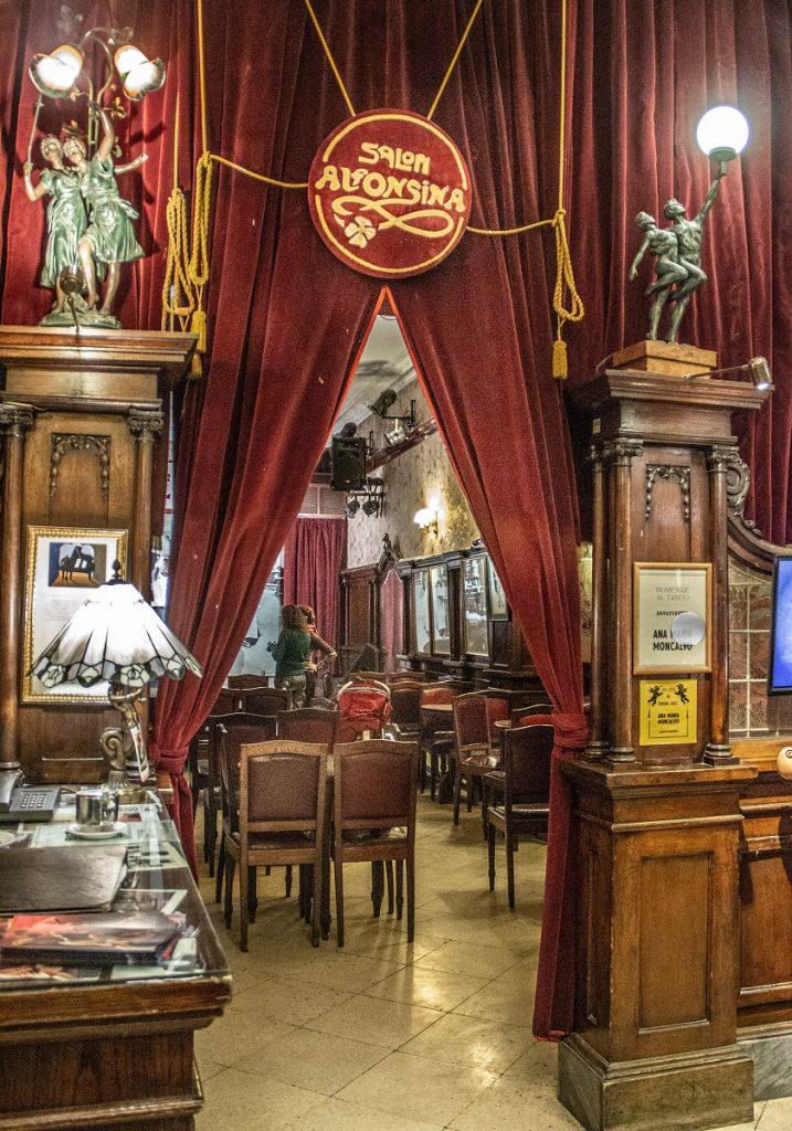 porta com cortinas de veludo deixando entrever a sala interior com cadeiras e um palco - tango barato