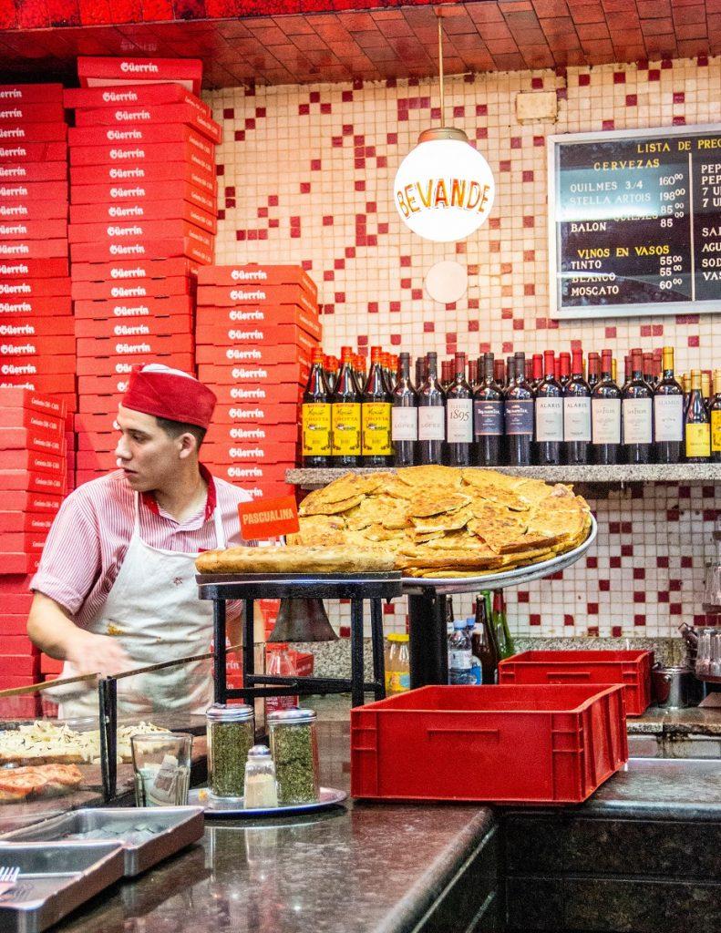 pizzaiolo no balcao e prateleira com vinhos ao fundo - cubierto Buenos Aires