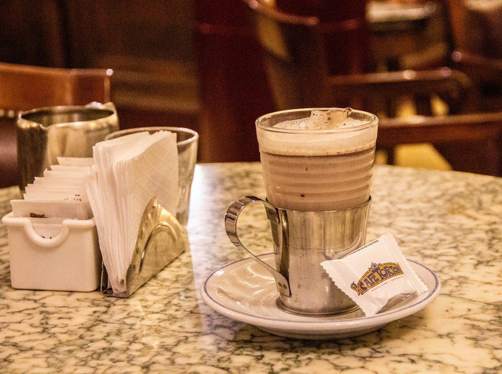 Copo com cafe com leite em uma mesa - cubierto Buenos Aires