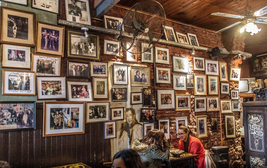 Bar com a parede coberta de retratos antigos - o que fazer em Buenos Aires com chuva