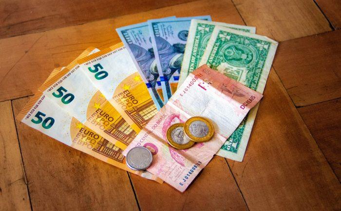 notas de euro, real e dolar em uma mesa - qual moeda levar para buenos aires