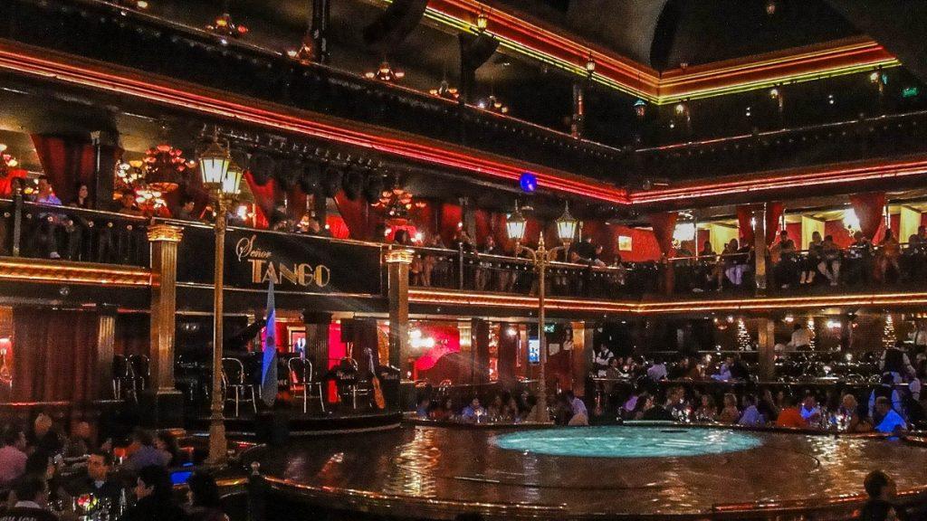 Ambiente de um show de tango: palco ao centro e pessoas em mesas ao redor - tango barato