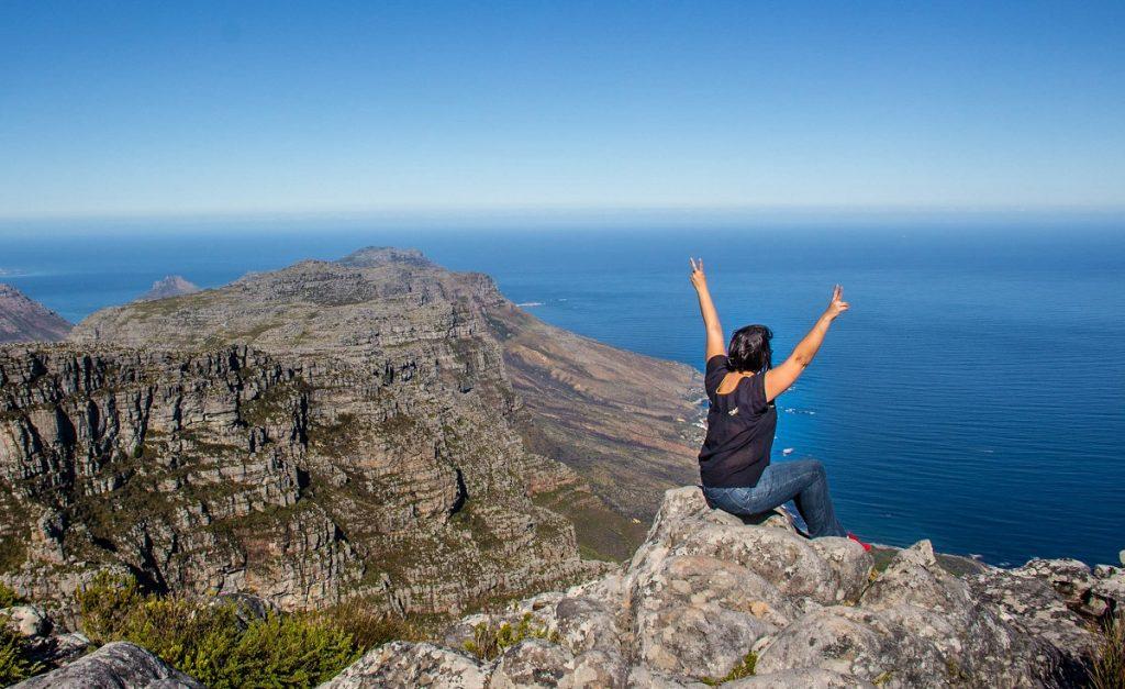 mulher de costas com bracos levantados em cima de paredao de rochas com mar ao fundo - visitar table mountain