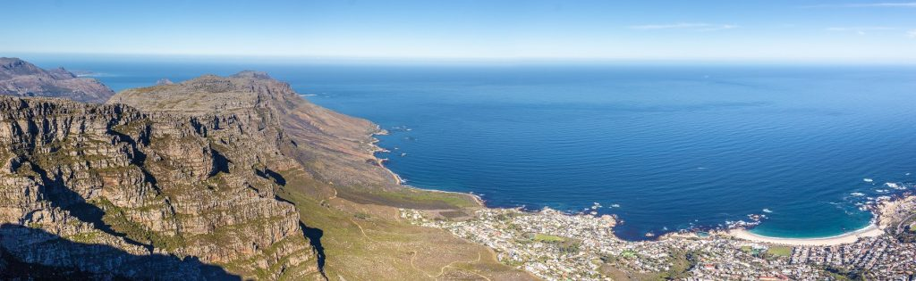 foto tirada do topo de uma montanha mostrando mar ao fundo - visitar table mountain