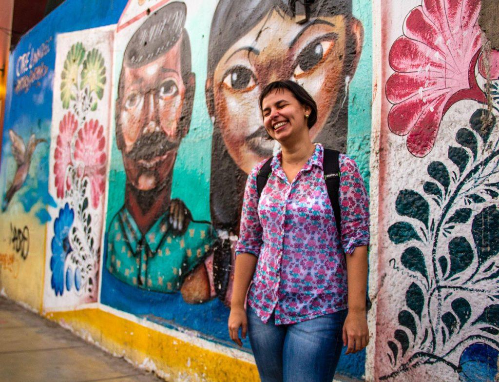 Mulher rindo em frente a parede com grafitti - cinco anos como nômade digital