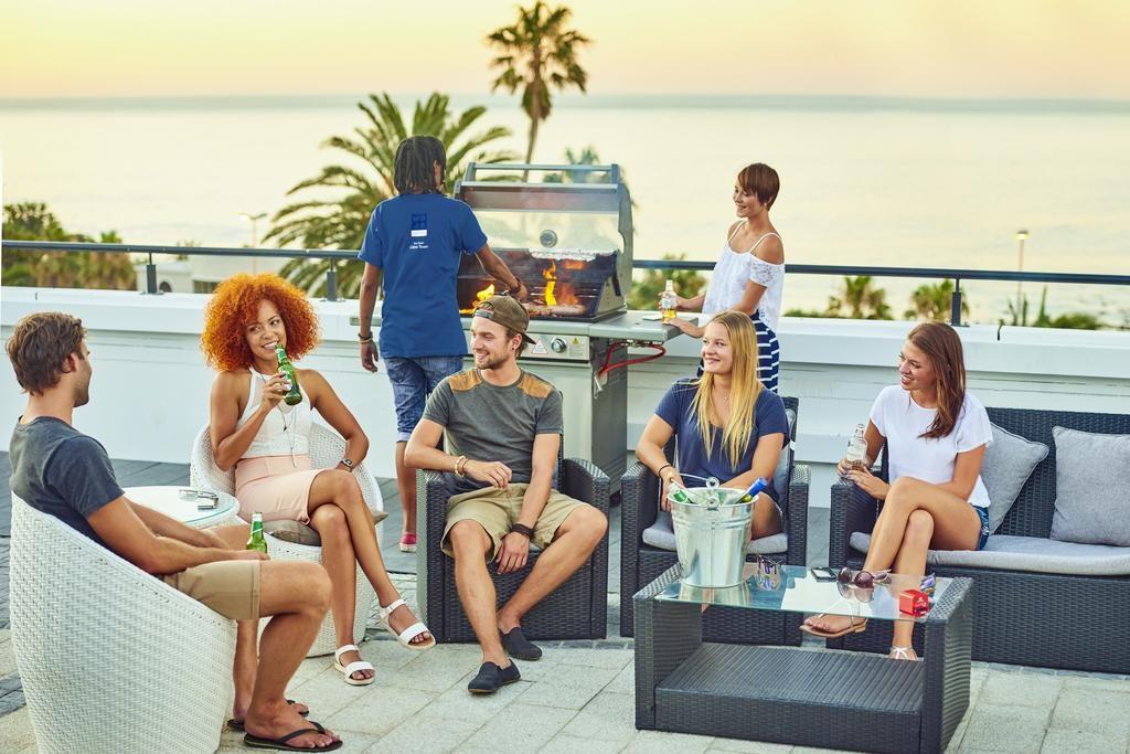 grupo de 6 jovens conversando ao redor de uma mesa. Onde ficar em Cape Town