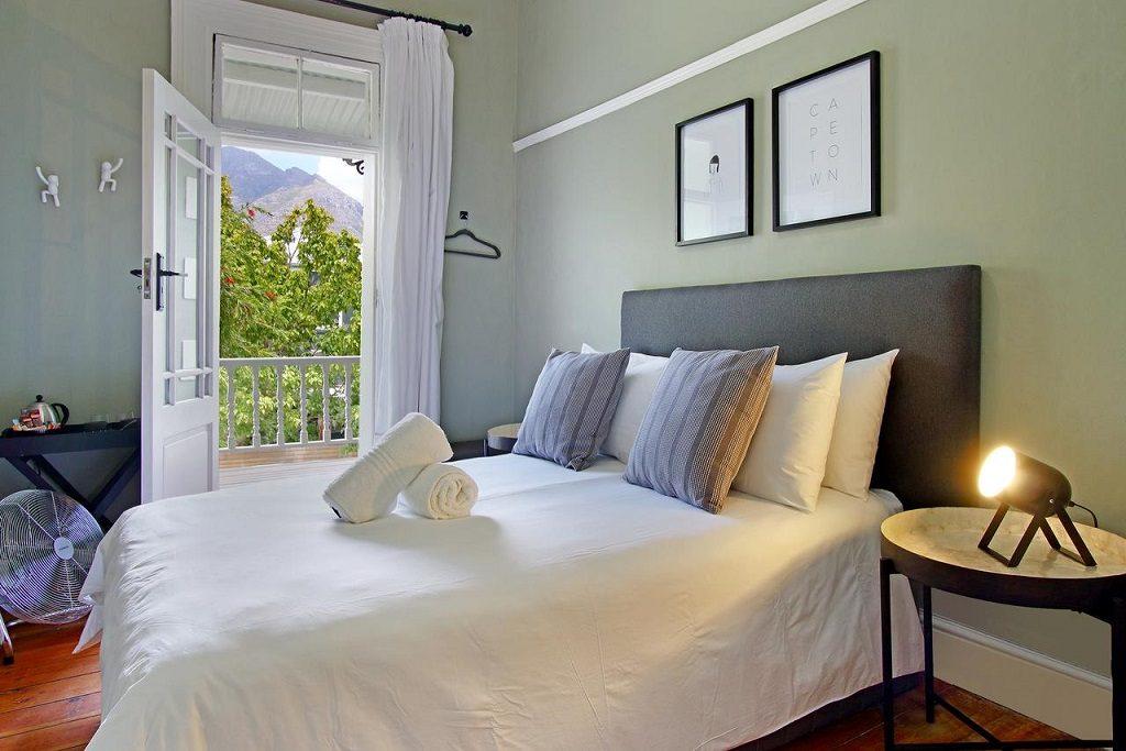 cama de casal em um quarto com janelão. Onde ficar em Cape Town
